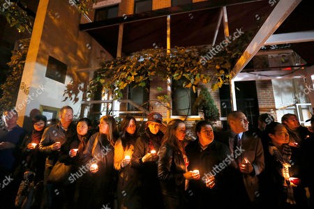 Friends and former employees of Chicago chef Charlie Trotter gather outside Trotter's former restaurant for a candlelight memorial, in Chicago. Trotter, 54, died Tuesday, a year after closing his namesake Chicago restaurant that was credited with putting his city at the vanguard of the food world and training dozens of the nation's top chefs, including Grant Achatz and Graham Elliot
