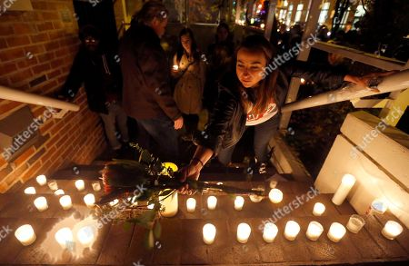 Jenifer Trotter, sister-in-law to Chicago Chef Charlie Trotter, places a bouquet of flowers with candles on the steps of Trotter's former restaurant after friends and former employees placed them there after a candle light tribute to Trotter, in Chicago. Trotter, 54, died Tuesday, a year after closing his namesake Chicago restaurant that was credited with putting his city at the vanguard of the food world and training dozens of the nation's top chefs, including Grant Achatz and Graham Elliot