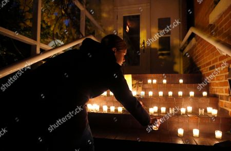 A woman places a candle on the steps of Chicago Chef Charlie Trotter's former restaurant after friends and former employees of Trotter's placed them there after a candle light tribute to Trotter, in Chicago. Trotter, 54, died Tuesday, a year after closing his namesake Chicago restaurant that was credited with putting his city at the vanguard of the food world and training dozens of the nation's top chefs, including Grant Achatz and Graham Elliot
