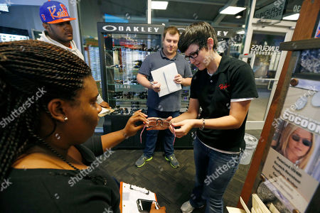 Mary Gates, Kyona Clark, Jordan Rimmer, James Wood Mary Gates, manager of Sunglass Warehouse, demonstrates the proper application of a clip-on shade to new employee Kyona Clark, left, as employees James Wood, second from right, and Jordan Rimmer, second from left, watch during a final training session at Mississippi's largest outlet center, The Outlets of Mississippi,, in Pearl, Miss. The $80 million center features more than 80 designer and name-brand stores