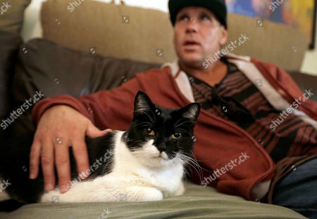 Mike Kelley, Andy On, Mike Kelley strokes his 10-year-old cat Andy, on the sofa in his living room on the evening when veterinarian Dr. Mary Gardner came to euthanize the animal, in Newport Beach, Calif. A few weeks earlier, Andy didn't greet Kelley at the door as usual and was soon diagnosed with liver disease, which meant euthanasia. It happened with the help of Gardner, co-founder of Lap of Love Veterinary Hospice, the country's first organized network of veterinarians who provide hospice and end of life care in the pet's home
