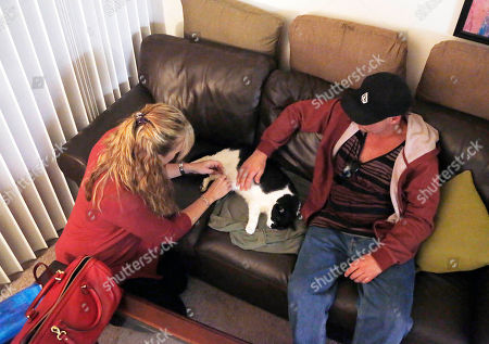 Mary Gardner, Mike Kelley, Andy On, veterinarian Dr. Mary Gardner looks for a vein to make an injection on Mike Kelley's cat Andy on the living room sofa at his home in Newport Beach, Calif. A few weeks earlier, 10-year-old Andy didn't greet Kelley at the door as usual and was soon diagnosed with liver disease, which meant euthanasia. It happened with the help of Gardner, co-founder of Lap of Love Veterinary Hospice, the country's first organized network of veterinarians who provide hospice and end of life care in the pet's home