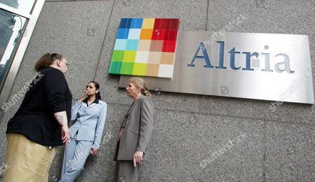 "Stock Image of People smoke near the logo for Altria Group Inc., the parent of tobacco company Phillip Morris, at the companies offices in New York. An Illinois appellate court on reinstated a decade-old $10.1 billion verdict in a class-action lawsuit against Phillip Morris USA that found the nation's biggest cigarette maker misled customers about ""light"" and ""low tar"" designations. Philip Morris swiftly decried Tuesday's ruling by a three-judge panel of the Mount Vernon-based 5th District Appellate Court, saying it would ask the Illinois Supreme Court to review the matter"