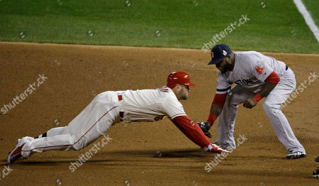 St. Louis Cardinals' Matt Holliday is tagged out at first by Boston Red Sox's David Ortiz during the third inning of Game 3 of baseball's World Series against the Boston Red Sox, in St. Louis. Holliday rounded first on a dropped ball and was thrown out