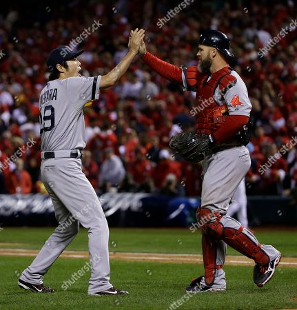 Boston Red Sox relief pitcher Koji Uehara celebrates with David Ross after St. Louis Cardinals left fielder Matt Holliday flied out to right field to end Game 5 of baseball's World Series, in St. Louis. The Red Sox won 3-1 to take a 3-2 lead in the series