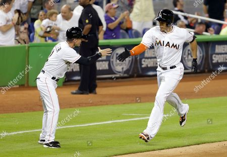 Giancarlo Stanton, Brett Butler Miami Marlins third base coach Brett Butler, left, greets Giancarlo Stanton as he rounds third base after hitting a two-run home run during the third inning of a baseball game against the Atlanta Braves, in Miami