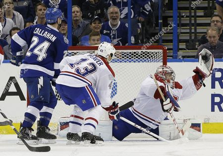Montreal Canadiens goalie Carey Price (31) makes a diving save on a shot as defenseman Mike Weaver (43) blocks Tampa Bay Lightning right wing Ryan Callahan (24) during the third period of an NHL hockey game, in Tampa, Fla