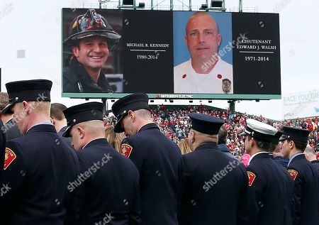 Boston firefighters bow their heads during a moment of silence for fallen colleagues Michael Kennedy and Edward Walsh during pre-game ceremonies before a baseball game between the Boston Red Sox and the Milwaukee Brewers on Opening Day at Fenway Park in Boston