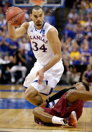 Stock Photo of Perry Ellis Kansas' Perry Ellis (34) passes the ball after getting tripped up by Eastern Kentucky's Tommy Matthews during the first half of a second-round game in the NCAA college basketball tournament, in St. Louis