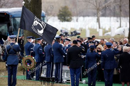 The POW-MIA flag flies during a group burial service for Air Force Capt. Valmore W. Bourque, Air Force 1st Lt. Robert G. Armstrong, Air Force Staff Sgt. Ernest J. Halvorson, Air Force Staff Sgt. Theodore B. Phillips, Air Force Airman 1st Class Eugene Richardson, Army Staff Sgt. Lawrence Woods, and Army Pfc. Charles P. Sparks, at Arlington National Cemetery in Arlington, Va. The seven service members, along with 1st Lt. Edward J. Krukowiski, were aboard a C-123 Provider aircraft that crashed on Oct. 24, 1964, when it was struck by enemy fire while resupplying the U.S. Special Forces camp at Bu Prang, Vietnam
