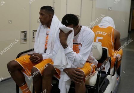 Tennessee guard Josh Richardson, left, and Jordan McRae look down in the cart as they head to the locker room after an NCAA Midwest Regional semifinal college basketball tournament game, in Indianapolis. Michigan won 73-71
