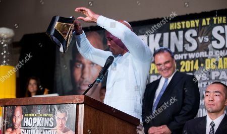 Bernard Hopkins, Beibut Shumenov Promoter Richard Schaefer, center, laughs as IBF light heavyweight boxing champion Bernard Hopkins, front left, takes the championship belt of WBA and IBA light heavyweight boxing champion Beibut Shumenov, right, of Kazakhstan, and moves it to his side of the table during a news conference in Washington, about their 175-pound unification fight to be held at the DC Armory in Washington on April 19