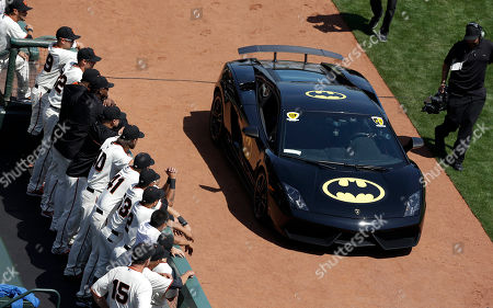 San Francisco Giants players, left, watch as the Batmobile drives into AT&T Park with Miles Scott, dressed as Batkid, who threw out the ceremonial first pitch before an opening day baseball game between the San Francisco Giants and the Arizona Diamondbacks in San Francisco, . On Nov. 15, 2013, Scott, a Northern California boy with leukemia, fought villains and rescued a damsel in distress as a caped crusader through The Greater Bay Area Make-A-Wish Foundation