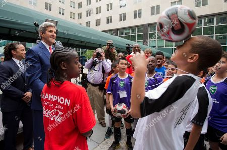 John Kerry, Cobi Jones A young soccer player heads the ball tossed to him by Secretary of State John Kerry, back second left, during a soccer clinic at the State Department in Washington, . Behind Kerry is Cobi Jones, State Department's sports envoy