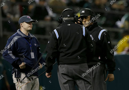 Mike Winters, Mark Wegner Umpires Mike Winters, center, and Mark Wegner, right, listen to headsets as the ruling that Cleveland Indians' Mike Aviles was out stealing second base against the Oakland Athletics is reversed after Indians manager Terry Francona challenged the call during the sixth inning of a baseball game in Oakland, Calif