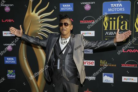 Stock Picture of DJ Ravi Drums poses for photographers as he walks the green carpet for the 15th annual International Indian Film Awards, in Tampa, Fla