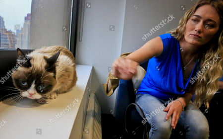 Tabatha Bundesen and her cat, Grumpy Cat,whose real name is Tardar Sauce, pose for a photograph on in New York. Bundesen says that Grumpy Cat's permanently grumpy-looking face is due to feline dwarfism