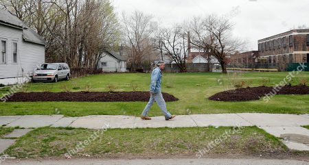 A man walks past an empty lot, which once was the home of Ariel Castro in Cleveland. The home was fortified with boarded-up windows and makeshift alarms where Castro held three women captive for nearly a decade