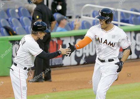Brett Butler, Giancarlo Stanton Miami Marlins' Giancarlo Stanton, right, is congratulated by third base coach Brett Butler as he rounds third base during the first inning of a baseball game against the San Diego Padres, in Miami