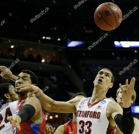 Dayton forward/center Jalen Robinson (12) and Stanford forward Dwight Powell (33) vie for a loose ball during the first half in a regional semifinal game at the NCAA college basketball tournament, in Memphis, Tenn