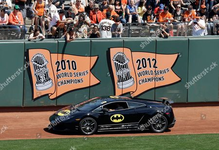 Stock Image of The Batmobile in the AT&T Park outfield with Miles Scott, dressed as Batkid, who threw out the ceremonial first pitch before an opening day baseball game between the San Francisco Giants and the Arizona Diamondbacks in San Francisco, . On Nov. 15, 2013, Scott, a Northern California boy with leukemia, fought villains and rescued a damsel in distress as a caped crusader through The Greater Bay Area Make-A-Wish Foundation