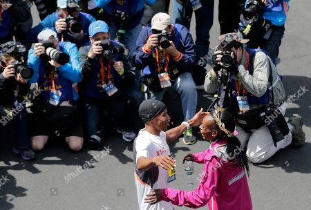 Meb Keflezighi, left, of San Diego, Calif., and Rita Jeptoo, of Kenya, start to embrace after winning their respective divisions of the 118th Boston Marathon in Boston