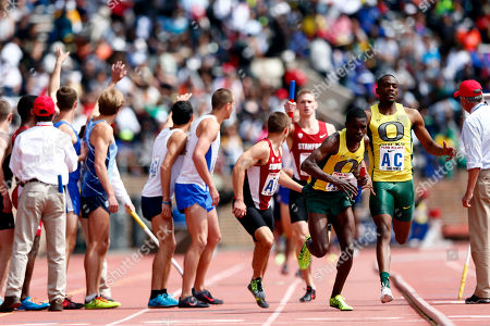 Mike Berry, Boru Guyota Oregon's Mike Berry, right, hands off the baton to Boru Guyota, second right, during the College Men's Distance Medley Championship of America at the Penn Relays athletics meet, in Philadelphia. Oregon won with a time of 9:25.40