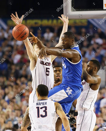 Niels Giffey, Shabazz Napier, Julius Randle Kentucky forward Julius Randle (30) passes the ball against Connecticut guard Niels Giffey (5) and guard Shabazz Napier (13) during the first half of the NCAA Final Four tournament college basketball championship game, in Arlington, Texas