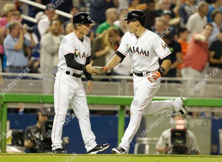 Brett Butler, Derek Dietrich Miami Marlins' Derek Dietrich, right, shakes hands with third base coach Brett Butler after hitting a three-run home run during the fourth inning of a baseball game against the Washington Nationals, in Miami