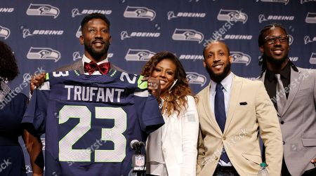 Marcus Trufant, Desmond Trufant, Isaiah Trufant Seattle Seahawks' Marcus Trufant, left, holds up a team jersey as he stands with his wife Jessica and brothers Isaiah, second right, and Desmond to start a news conference announcing his retirement from football after signing with the team a day earlier, in Renton, Wash. Trufant started 125 games in a Seattle career that lasted from 2003 to 2012. The cornerback was a first-round pick in 2003 out of Washington State and immediately moved into the starting lineup, playing a key role on the 2005 team that advanced to the franchise's first Super Bowl