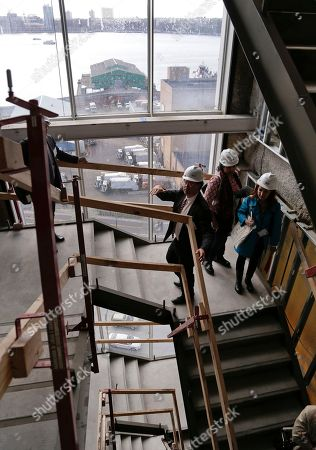 Stock Image of Whitney Museum director Adam Weinberg, center, explains the architectural design of a staircase during a tour of the future site for the Whitney Museum, in New York. The museum will open in its new location in lower Manhattan in the spring of 2015