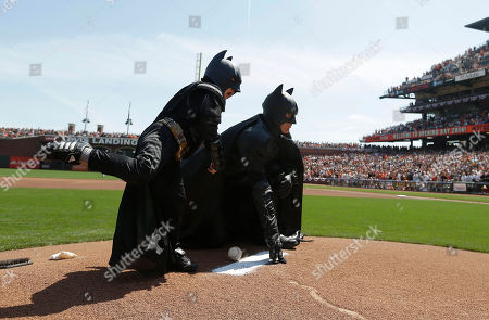 Miles Scott, dressed as Batkid, left, throws the ceremonial first pitch next to Batman before an opening day baseball game between the San Francisco Giants and the Arizona Diamondbacks in San Francisco, . On Nov. 15, 2013, Scott, a Northern California boy with leukemia, fought villains and rescued a damsel in distress as a caped crusader through The Greater Bay Area Make-A-Wish Foundation