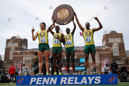 Stock Image of Mac Fleet, Boru Guyota, Edward Cheserek, Mike Berry From left, Oregon's Mac Fleet, Boru Guyota, Edward Cheserek and, Mike Berry pose for a photographs on the podium after winning the the College Men's Distance Medley Championship of America at the Penn Relays athletics meet, in Philadelphia. Oregon won with a time of 9:25.40
