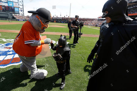Miles Scott, dressed as Batkid, center, greets San Francisco Giants mascot Lou Seal after Scott threw the ceremonial first pitch before an opening day baseball game between the Giants and the Arizona Diamondbacks in San Francisco, . On Nov. 15, 2013, Scott, a Northern California boy with leukemia, fought villains and rescued a damsel in distress as a caped crusader through The Greater Bay Area Make-A-Wish Foundation