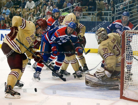 Ian McCoshen, Thatcher Demko, Josh Holmstrom Boston College's Ian McCoshen, far left, clears the puck from the crease while goalie Thatcher Demko protects the net against UMass Lowell's Josh Holmstrom (12) late in the third period of the NCAA Northeast Regional hockey final in Worcester, Mass., . Boston College won 4-3