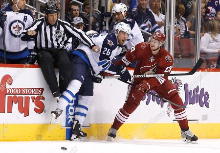 Oliver Ekman-Larsson, Blake Wheeler, Jay Sharrers Phoenix Coyotes' Oliver Ekman-Larsson (23), of Sweden, shoves Winnipeg Jets' Blake Wheeler (26) into linesman Jay Sharrers during the first period of an NHL hockey game, in Glendale, Ariz. The Jets defeated the Coyotes 2-1 in a shootout
