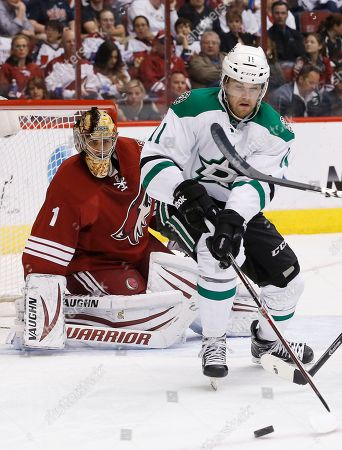 Stock Picture of Dustin Jeffrey, Thomas Greiss As Phoenix Coyotes' Thomas Greiss (1), of Germany, protects the goal, Dallas Stars' Dustin Jeffrey (11) tries to control the puck during the second period of an NHL hockey game, in Glendale, Ariz. The Coyotes defeated the Stars 2-1
