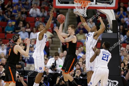 Mercer forward Jakob Gollon (20) passes the ball as Duke forward Jabari Parker, right, and Duke forward Rodney Hood (5) defend during the second half of an NCAA college basketball second-round game, in Raleigh, N.C