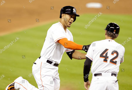 Giancarlo Stanton, Brett Butler Miami Marlins' Giancarlo Stanton, left, rounds third base after hitting a three-run home run during the first inning of a baseball game against the Washington Nationals, in Miami. At right is third base coach Brett Butler