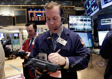 James Doherty Trader James Doherty, right, works on the floor of the New York Stock Exchange . U.S. stock indexes are slipping lower in early trading Thursday as investors pick over a mixed batch of corporate earnings reports