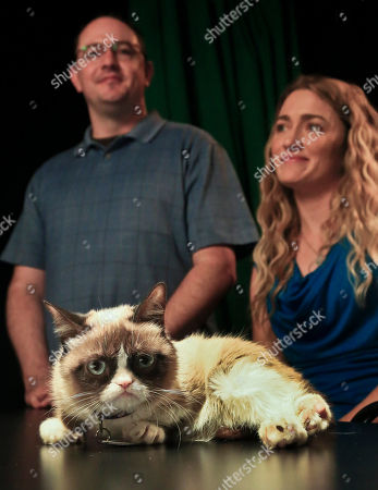 Grumpy Cat Bryan Bundesen, left and his sister Tabatha Bundesen pose with Grumpy Cat, whose real name is Tardar Sauce, as they prepare for an interview on in New York. Tabatha Bundesen says that Grumpy Cat's permanently grumpy-looking face is due to feline dwarfism