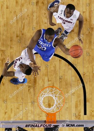 Julius Randle, Amida Brimah, Terrence Samuel Kentucky forward Julius Randle, center, drives to the basket between Connecticut's Amida Brimah, left, and Terrence Samuel during the first half of the NCAA Final Four tournament college basketball championship game, in Arlington, Texas