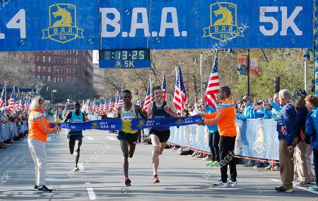 Stock Image of Dejen Gebremeskel, left, of Ethiopia, breaks the tape ahead of Ben True, of Hanover, N.H., to win the 5-kilometer run, in Boston, in advance of Monday's 118th Boston Marathon