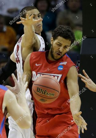 Dayton forward Devin Oliver (5) works against Stanford forward Dwight Powell (33) during the second half in a regional semifinal game at the NCAA college basketball tournament, in Memphis, Tenn