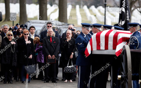 Steven Woods, Lisa Szymanski Family members including Steven Woods, third from left, and Lisa Szymanski, fourth from left, stand as the casket is removed from the caisson, during a group burial service for Air Force Capt. Valmore W. Bourque, Air Force 1st Lt. Robert G. Armstrong, Air Force Staff Sgt. Ernest J. Halvorson, Air Force Staff Sgt. Theodore B. Phillips, Air Force Airman 1st Class Eugene Richardson, Army Staff Sgt. Lawrence Woods, and Army Pfc. Charles P. Sparks, at Arlington National Cemetery in Arlington, Va. The seven service members, along with 1st Lt. Edward J. Krukowiski, were aboard a C-123 Provider aircraft that crashed on Oct. 24, 1964, when it was struck by enemy fire while resupplying the U.S. Special Forces camp at Bu Prang, Vietnam