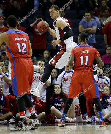 Stanford forward Dwight Powell (33) works on a save as Dayton forward/center Jalen Robinson (12) and Dayton guard Scoochie Smith (11) look on during the first half in a regional semifinal game at the NCAA college basketball tournament, in Memphis, Tenn