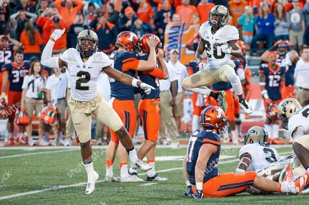 Illinois punter Ryan Frain (13) consoles place kicker Chase McLaughlin (43) as Purdue cornerback Da'Wan Hunte (2) and cornerback David Rose (20) celebrate McLaughlin's missed last second field goal attempt during the second half of an NCAA college football game, in Champaign, Ill. Purdue defeated Illinois 34-31 in overtime