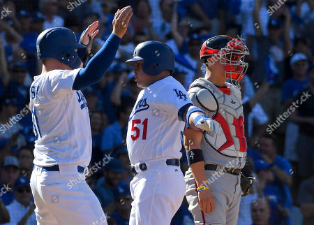 Los Angeles Dodgers' Carlos Ruiz, left, celebrates after his two-run home run with Joc Pederson as Washington Nationals catcher Jose Lobaton, right, looks away during the fifth inning in Game 3 of baseball's National League Division Series in Los Angeles