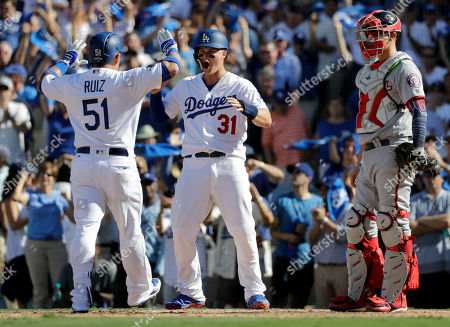 Los Angeles Dodgers' Carlos Ruiz, left, celebrates after his two-run home run with Joc Pederson as Washington Nationals catcher Jose Lobaton, right, during the fifth inning in Game 3 of baseball's National League Division Series in Los Angeles