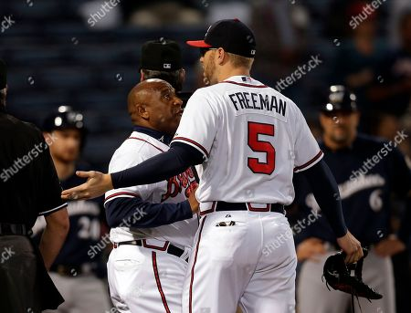 Freddie Freeman, Terry Pendelton Atlanta Braves first baseman Freddie Freeman (5) is restrained by Atlanta Braves first base coach Terry Pendleton (9) during an argument with Milwaukee Brewers in the first inning of a baseball game in Atlanta